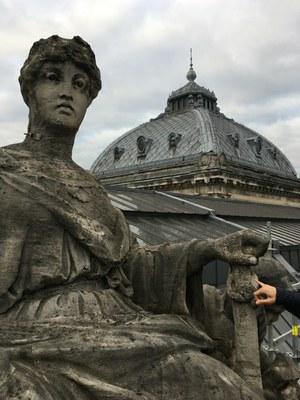 statue sur la toiture de al bourse avec la coupole en arrière-plan